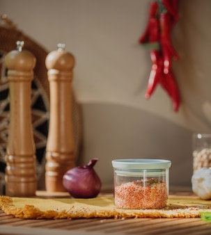 Side view of a glass jar with red lentils on a wooden table