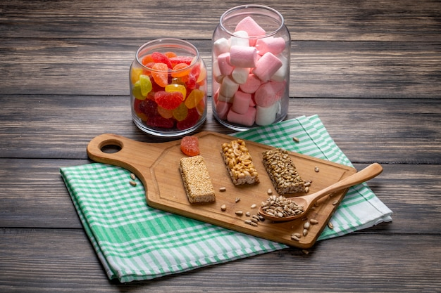 Side view of glass jars with marmalade candies and marshmallow and sweet kozinaki of sesame sunflower seeds and peanuts on a wooden board on rustic