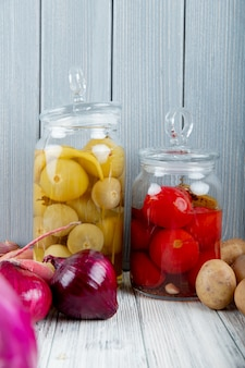Side view of glass jars with sour tomatoes and onions potatoes on wooden surface and background with copy space