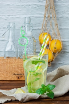 Side view glass of lemon juice with wooden crate and lemons on wooden and white surface. vertical