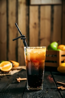 Side view of glass of long island cocktail with a black straw on the wooden background, vertical, side view
