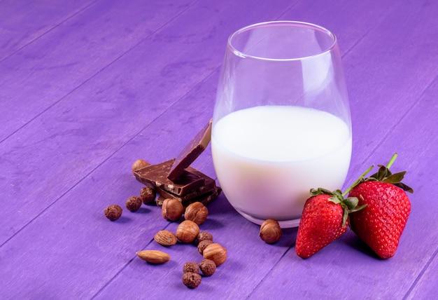 Vista laterale di un bicchiere di latte con nocciole fresche fragole mature e cioccolato fondente su fondo di legno viola