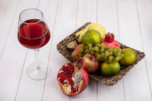 Вид сбоку стакан гранатового сока с гранатами, виноградом, мандаринами и грушами в корзине на белой стене