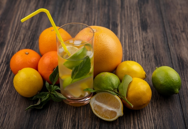 レモンライムとミントのスライスと黄色いわらとグレープフルーツとオレンジの木製の背景に水の側面図ガラス