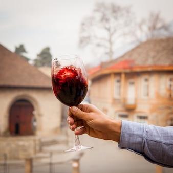 Vista laterale bicchiere di vino rosso un uomo tiene in mano un bicchiere di vino rosso