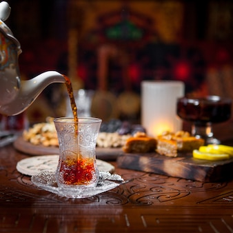 Side view glass of tea with baklava and lemon and jam in table