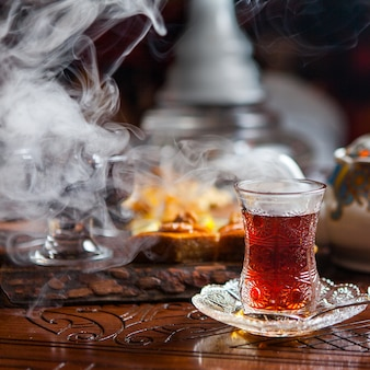 Side view glass of tea with baklava and smoke in table