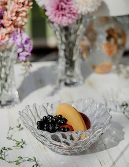 Vista laterale del vaso di vetro con l'uva e le banane della frutta su una tavola di legno bianca