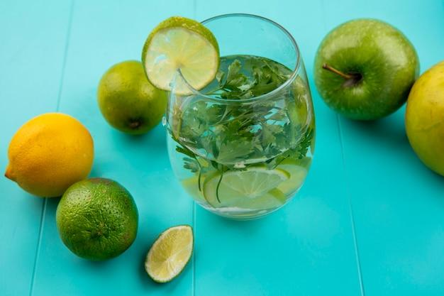 Vista laterale del bicchiere d'acqua con verdure e lime con limone su una superficie blu