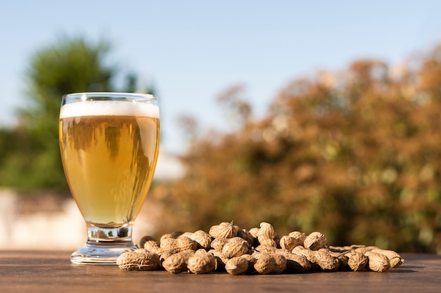 Side view glass with beer beside peanuts on table