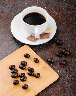 Side view of glazed chocolate nut candy scattered on a wooden board and a cup of coffee on black background