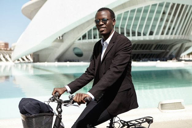 Side view of good-looking afro american employee cycling home on bike after working day in office. successful happy dark-skinned entrepreneur enjoying ride on bicycle, commuting to work in the morning