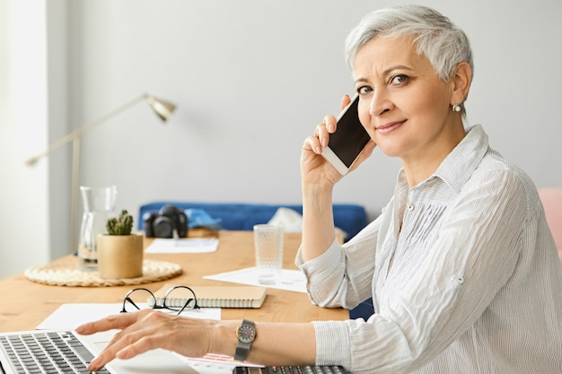 Side view of good looking middle aged female ceo in elegant blouse holding smart phone, speaking to client, enjoying conversation while working on laptop at office desk. technology and communication