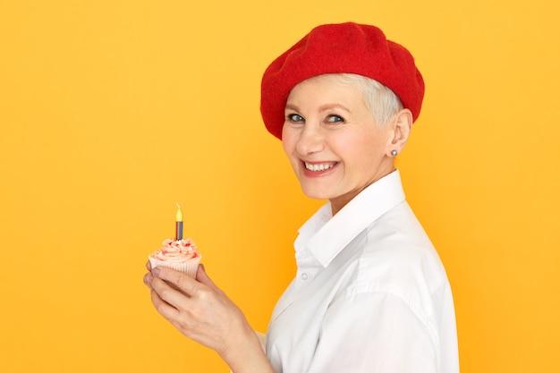 Vista laterale della splendida donna di mezza età uscita con i capelli tinti corti sotto il cappello rosso che fa desiderio che tiene il bigné di compleanno con una candela