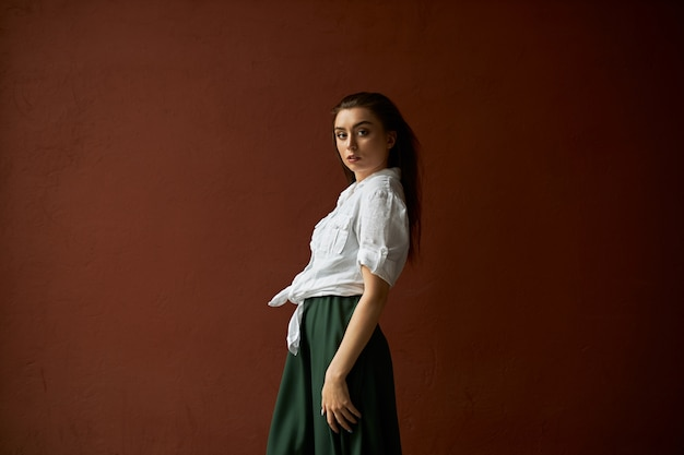 Side view of gorgeous slim young female in white shirt and skirt posing against copy space studio wall background for your advertisement having confident facial expression, looking at camera