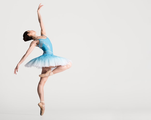 Side view of gracious ballerina dancing with copy space