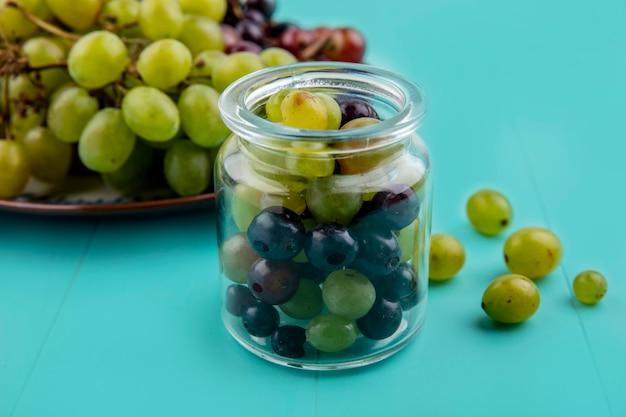 Vista laterale di acini d'uva in vaso e uva nel piatto su sfondo blu