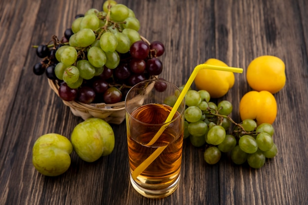 Vista laterale del succo d'uva in vetro e uva nel cestino con pluots e nectacots su fondo di legno