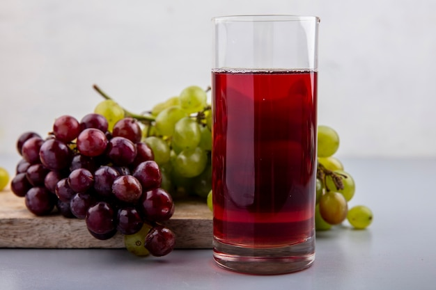 Side view of grape juice in glass and grapes on cutting board on gray surface and white background