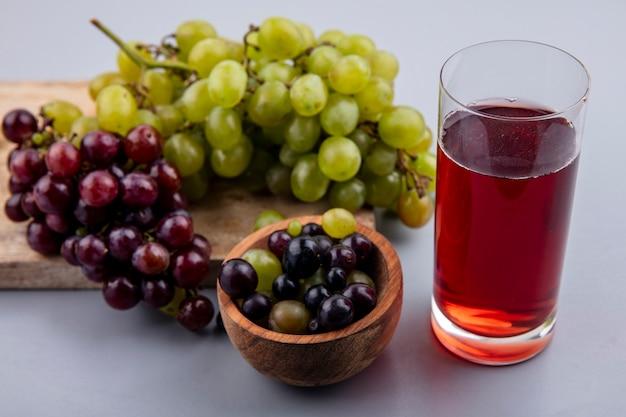 Vista laterale del succo d'uva in vetro e uva sul tagliere con ciotola di acini d'uva su sfondo grigio
