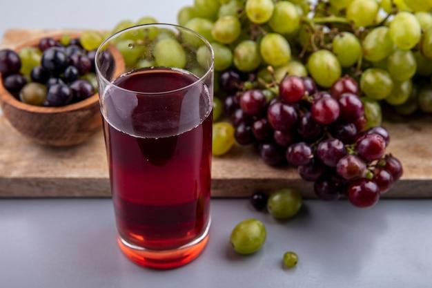 Vista laterale del succo d'uva in vetro e uva con ciotola di acini d'uva sul tagliere su sfondo grigio