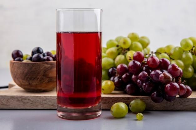 Vista laterale del succo d'uva in vetro e uva con ciotola di acini d'uva sul tagliere su superficie grigia e sfondo bianco