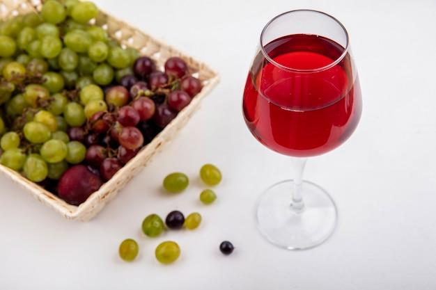 Vista laterale del succo d'uva nel bicchiere da vino e cesto di pluot e uva con acini d'uva su sfondo bianco