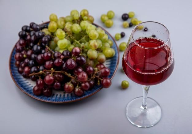 Vista laterale del succo d'uva nel bicchiere da vino e uva nel piatto e su sfondo grigio