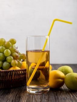 Vista laterale del succo d'uva con tubo per bere in vetro e cesto di uva nectacot con pluots su una superficie di legno e sfondo bianco