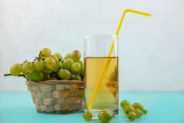 Vista laterale del succo d'uva con tubo per bere in vetro e cesto di uva con acini d'uva su superficie blu e sfondo bianco
