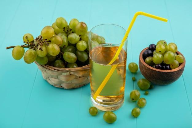 Vista laterale del succo d'uva con tubo per bere in vetro e cesto di uva con acini d'uva in una ciotola su sfondo blu