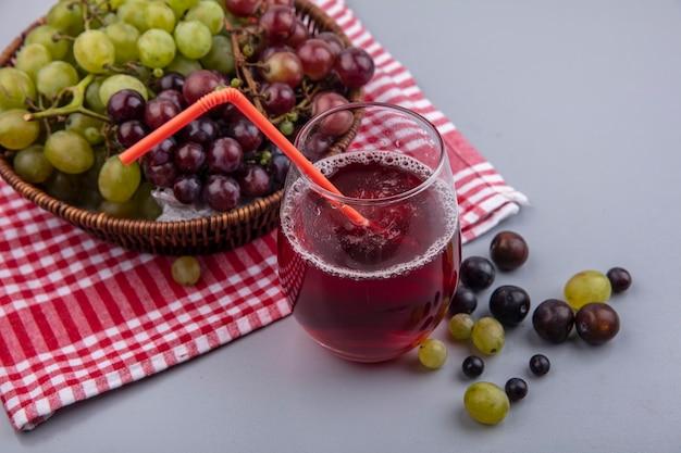 Vista laterale del succo d'uva con tubo per bere in vetro e cesto di uva su un panno plaid con acini d'uva su sfondo grigio