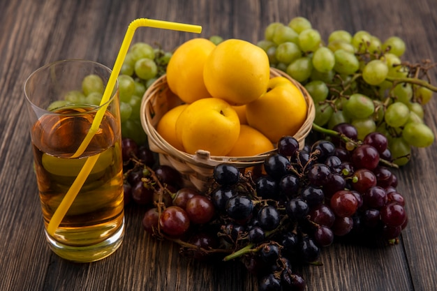 Vista laterale del succo d'uva con tubo per bere in vetro e cesto di nettacots con uva intorno su fondo di legno