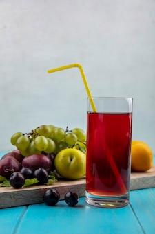 Vista laterale del succo d'uva con tubo per bere in vetro e uva nectacot pluots sul tagliere su superficie blu e sfondo bianco