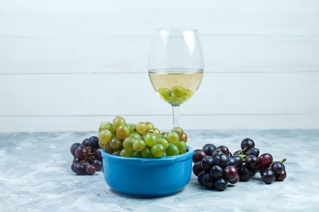 Side view grapes in bowl with a glass of wine on grungy grey and wooden background. horizontal