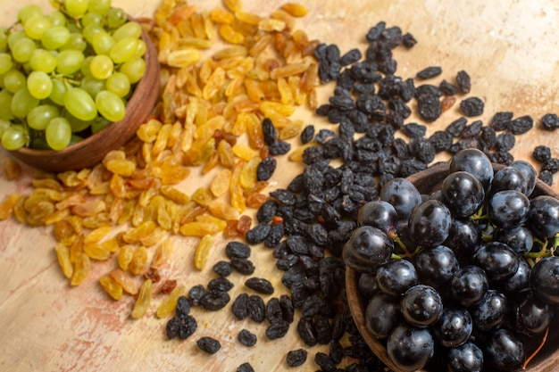 Vista laterale uva uva passa verde e nera grappoli di uva verde e nera nella ciotola
