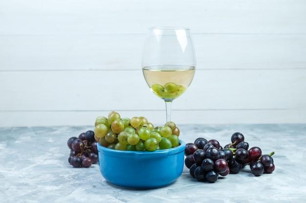 汚れた灰色と木製の背景にワインのグラスとボウルにブドウの側面図。水平