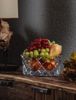 Side view of grapes with pears in a glass vase on a wooden cupboard on dark wall