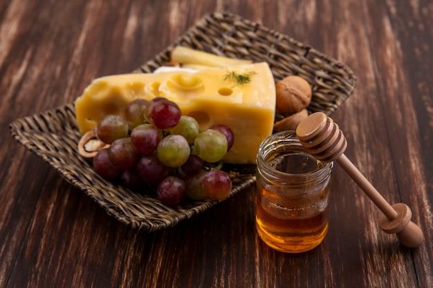 Vista laterale uva con varietà di formaggi e noci su un supporto con miele in un barattolo su un fondo di legno