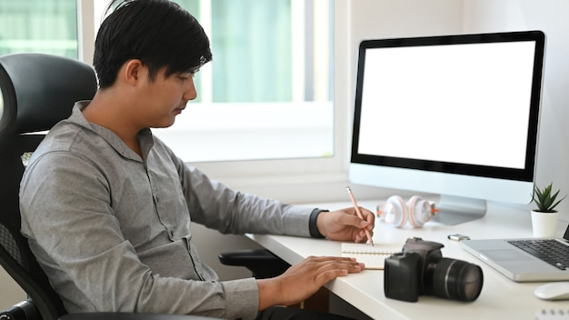 Side view of graphic designer or photographer is sitting in front of empty screen computer and taking notes in notebook.