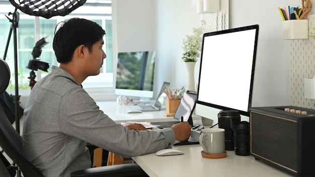 Side view of graphic designer or photographer is using  graphic table retouching a photo at his workspace.