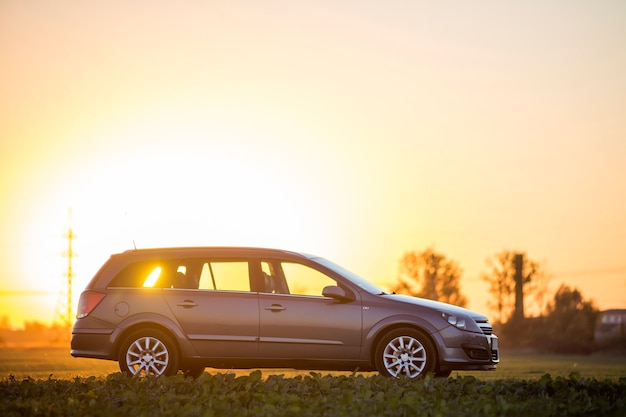 Side view of gray silver empty car parked in countryside on blurred rural landscape and bright orange clear sky at sunset copy space background.