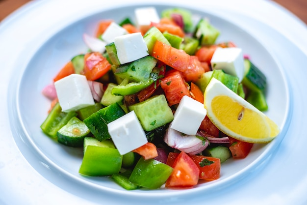 Side view greek salad with white cheese fresh cucumber tomato greens red onion and slice of lemon on a plate