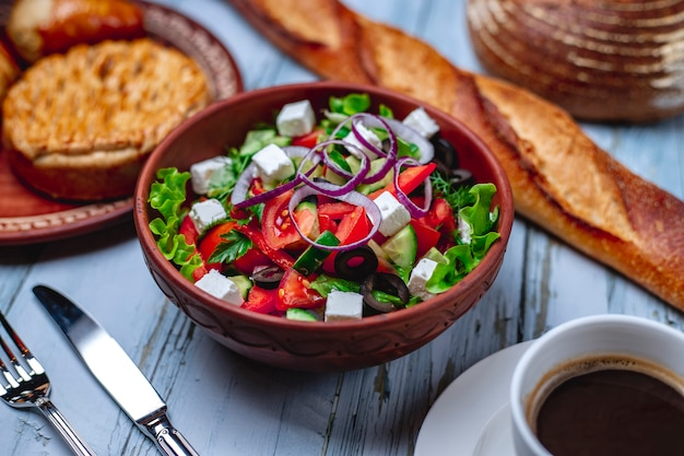 Side view greek salad with white cheese tomato red onion lettuce cucumber black olive and cup of coffee on the table
