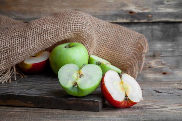 Взгляд со стороны зеленые и красные яблоки отрезали в половине на древесине, ткани и темной деревянной предпосылке. горизонтальный