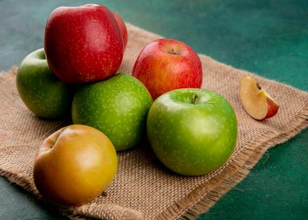 Вид сбоку зеленые и красные яблоки на бежевой салфетке на зеленом фоне
