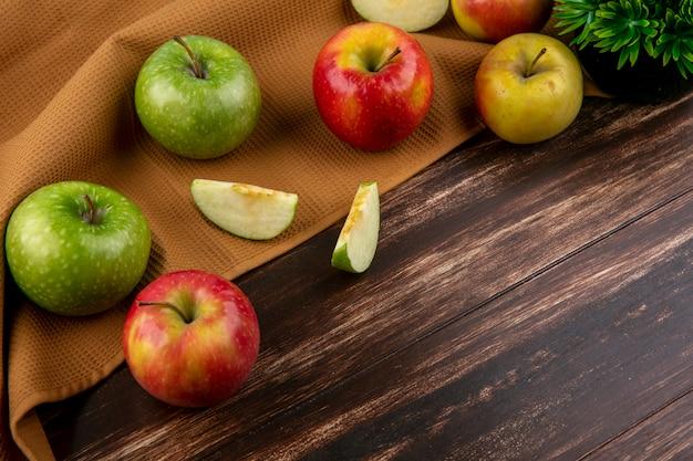 サイドビューの木製の背景に茶色のタオルの上に緑と赤のリンゴ