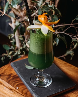Side view of green apple smoothie in glass on a wooden table