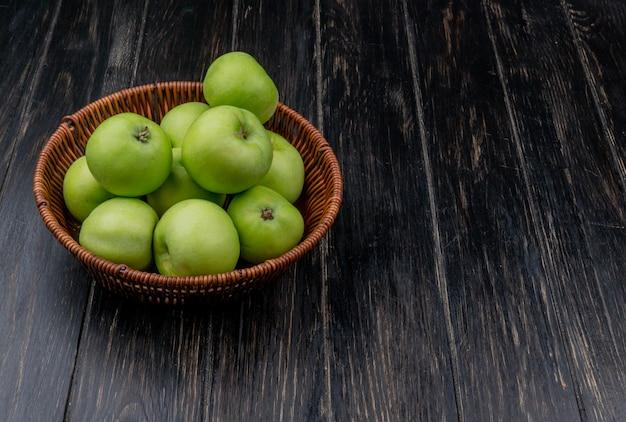 Vista laterale della merce nel carrello verde delle mele su fondo di legno con lo spazio della copia