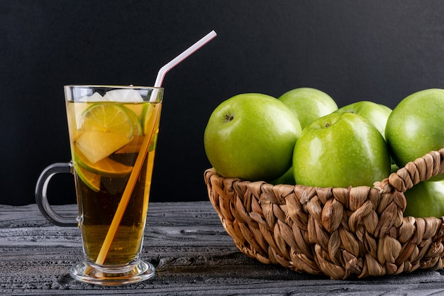 Side view green apples in beige straw basket and juice on gray wooden table and black